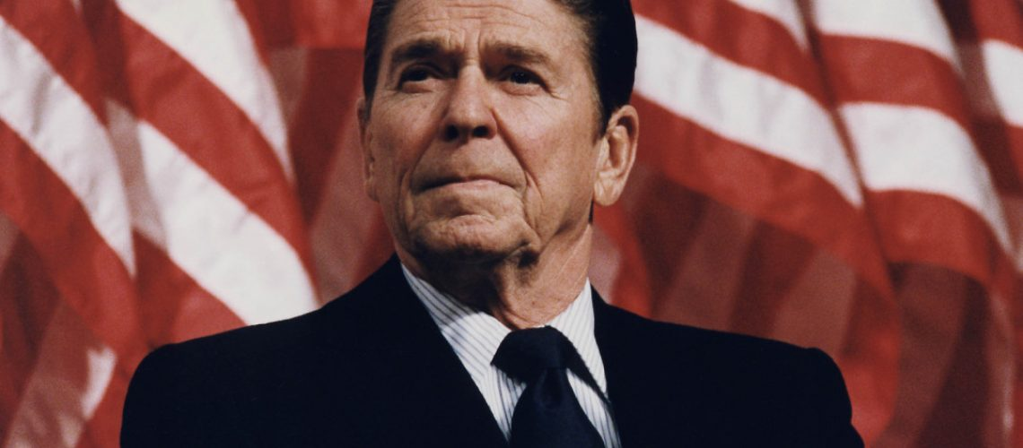 Ronald reagan in front of a flag