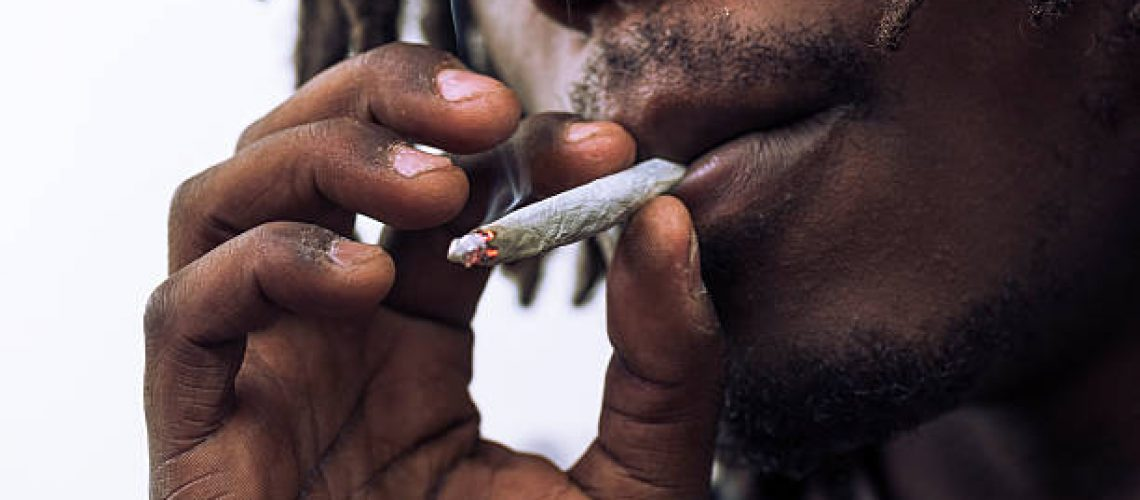 Black man smoking joint, with either marijuana or tobacco.